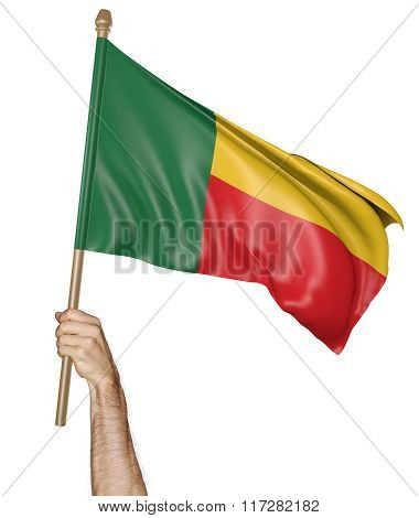 Hand proudly waving the national flag of Benin