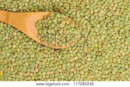 Wooden spoon and dry lentils healthy food background