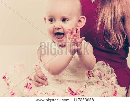 Happy Baby Girl On Mother Knees.