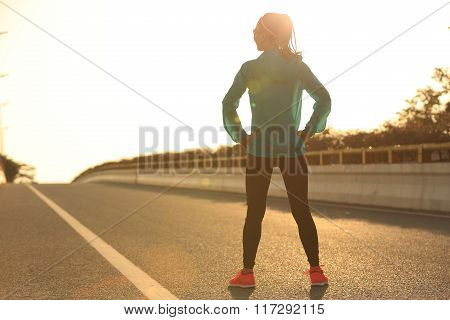 young fitness woman runner athlete standing on sunrise road with her hands on hips