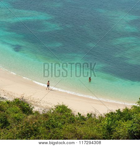Couple swimming in the turquoise sea on the beautiful tropic beach