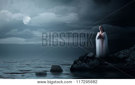 Young elven girl on night sea coast