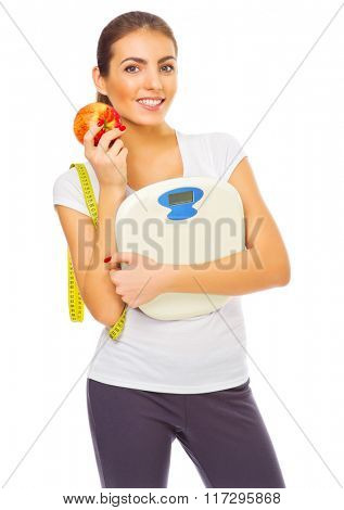 Young healthy woman with apple and scales isolated