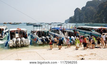 PHI PHI ISLANDS, THAILAND - CIRCA FEBRUARY, 2015: Speed boats with tourists on the shore of the island of Phi Phi Doh in the Andaman Sea. Island is very popular with tourists from all over the world