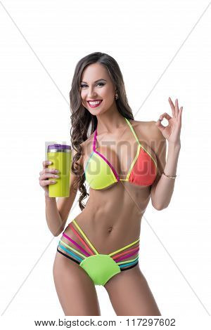 Sports nutrition. Sexy model shows gesture OK