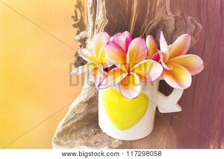 Pink Yellow Flower Plumeria Or Frangipani In Lovely Heart Pattern Cup On Timber