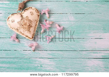 Background  With Little Flowers Hyacinths  And  Beige Decorative Heart On Turquoise Painted Wooden P