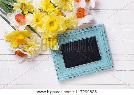Fresh  Spring Yellow Narcissus Flowers  And Empty Blackboard On White Wooden Planks.