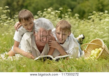 Family with book on summer grass