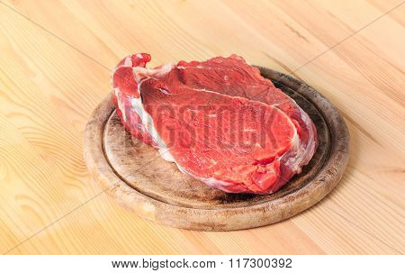 Red Slice Of Meat On Cutting Board