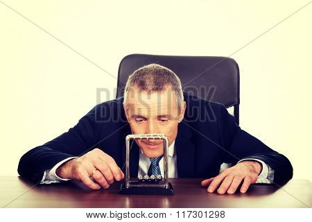 Businessman in office playing with newton balls