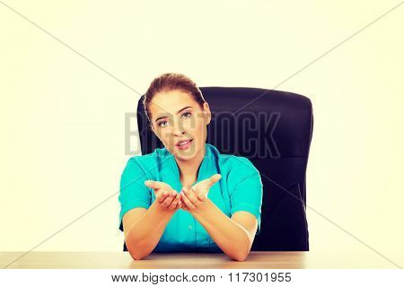 Young female doctor or nurse sitting behind the desk and talking with someone