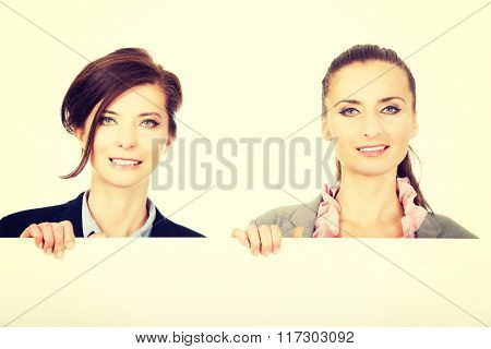 Two businesswomen carrying a big white board.