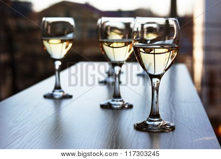 Glasses of wine on light blurred background