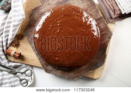 Tasty chocolate frosting cake on light table
