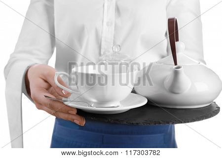 Waiter holding tray with cup and teapot on white background
