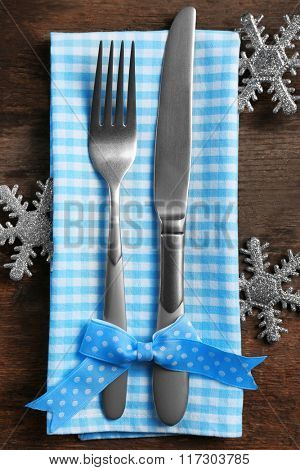 Christmas serving cutlery with napkin on a wooden background, close up