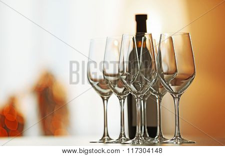 Empty wineglasses in a row and bottle on a table, close up