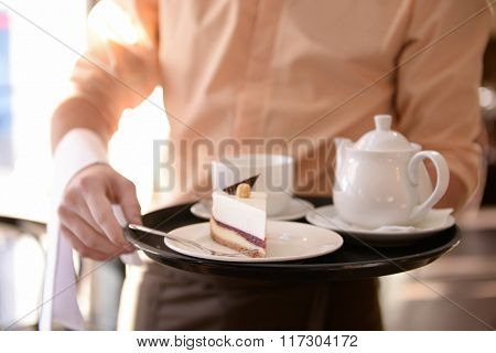 Waiter holding tray with teapot, cups and cake close up