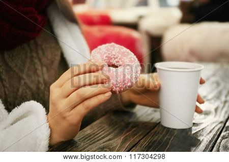 Female hands holding a cup of hot drink and tasty doughnut at the table