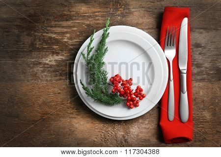 Christmas serving cutlery with napkin and plate on a wooden background