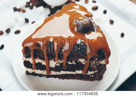 Piece of chocolate cake with caramel in white saucer closeup
