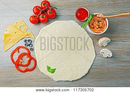 Fresh ingredients for pizza preparing on wooden table