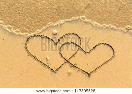 Two hearts drawn on the sand of a beach.