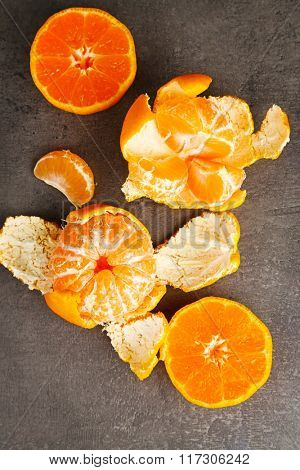 Bowl with fresh tangerines on dark metal table, close up