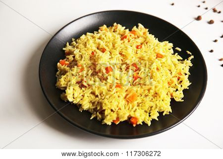 Stewed rice with a carrot on a black plate, close up