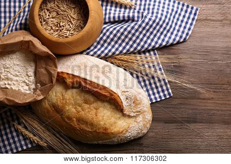Fresh baked bread, flour, wheat and napkin on the wooden background