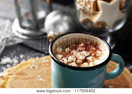 Mug of hot cacao with marshmallow and cookies on black table