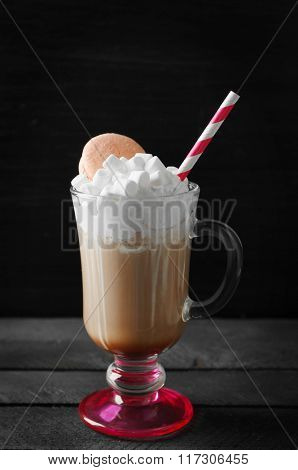 Cup of coffee with whipped cream and macaroon on black background