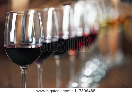 Many glasses of different wine in a row on bar counter