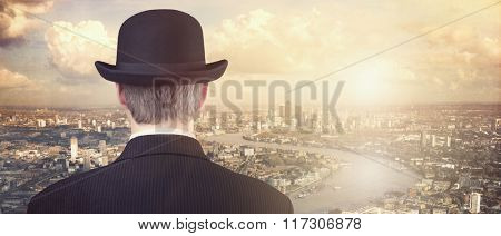 Businessman with bowler hat looking at financial city skyline concept for finance, investment, career and opportunity
