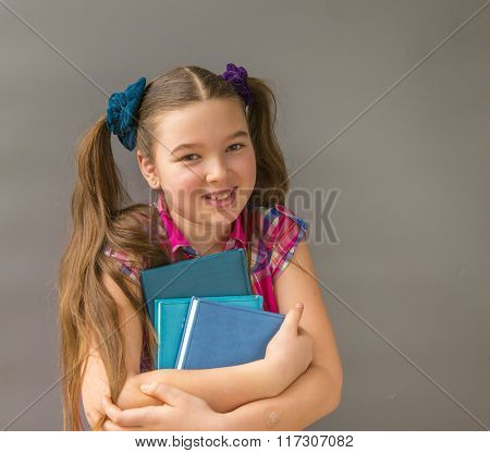 Portrait of cute schoolgirl smiling and holding book