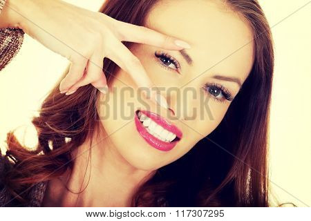 Young woman showing peace gesture.