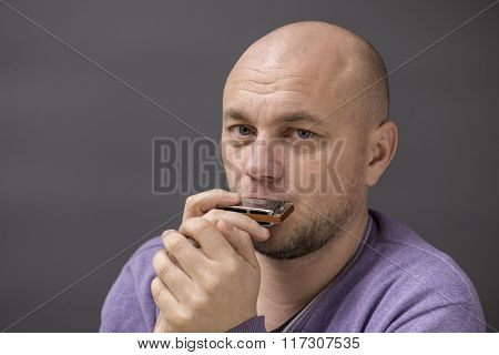 Portrait of a bald man with a harmonica in his mouth.