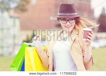 Young attractive happy shopper woman wearing hat and glasses holding shopping bags and take away coffee walking in the street