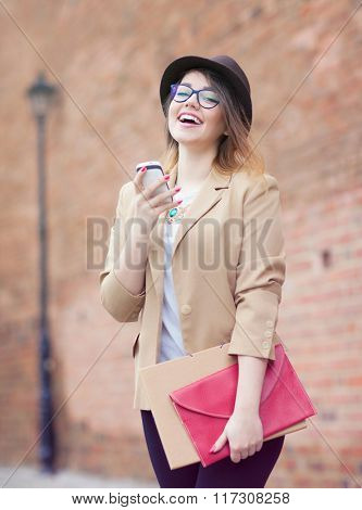 Young attractive happy laughing student woman wearing hat and glasses holding a briefcase using a smart phone in the street. Technology internet communication and social media concept.