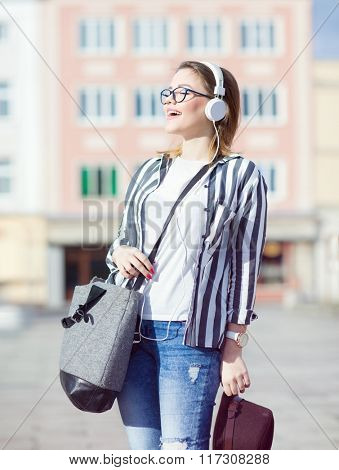 Young attractive happy laughing student woman wearing headphones and glasses holding a bag listening to music in the street.