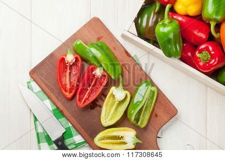 Fresh colorful bell peppers cooking on wooden table