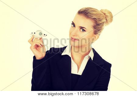 Beautiful businesswoman holding airplane miniature