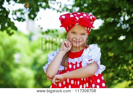 Portrait of a charming little girl looking at camera, on green summer background