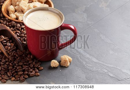 Coffee cup, beans and brown sugar on stone table. View with copy space