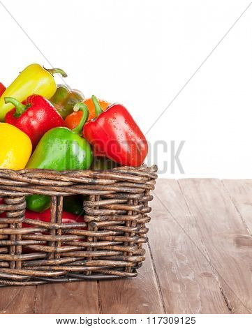 Fresh colorful bell peppers box on wooden table. Isolated on white background