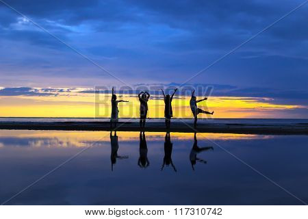 Silhouette of ladies show body language LOVE on the beach during a beautiful sunrise