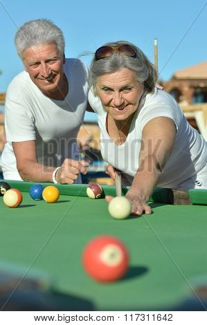 old couple playing billiard