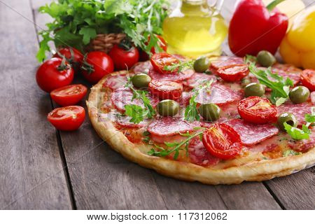 Delicious tasty pizza with ingredients on table, closeup