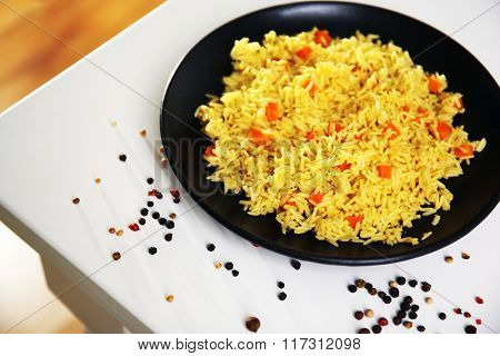 Stewed rice with a carrot on a black plate